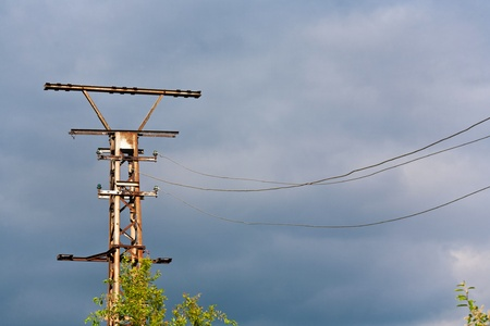 transformator: old rusty electrical tower with dark clouds