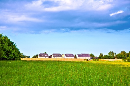 grass plot: noise protection wall with field and houses Stock Photo