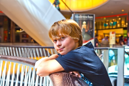 smiling boy inside a center resting against a balustrade Stock Photo - 10571565