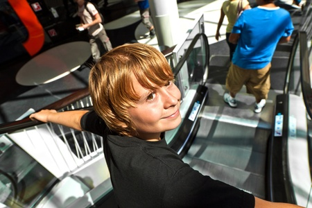 cute boy on a moving staircase in the shopping center photo