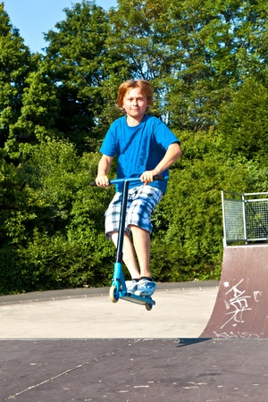 young boy going airborne with his scooter at the skate park photo