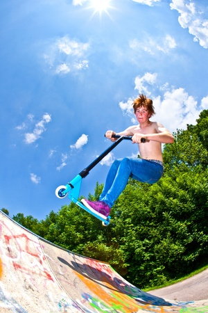 young boy going airborne with his scooter photo