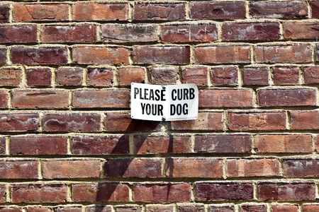 sign please curb your dog at a house wall Stock Photo - 10741683