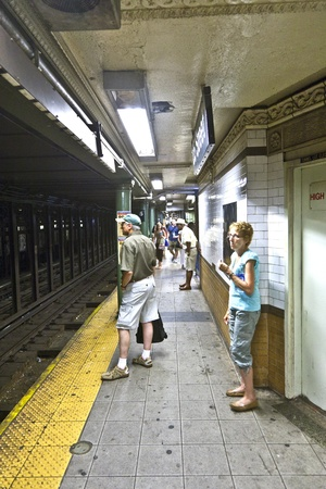 NEW YORK CITY - July 11: people wait fur subway in 135 street  on July 11, 2010 in New York City. The first underground line   opened on October 27, 1904 and is the forth busiest nowadays in the world.