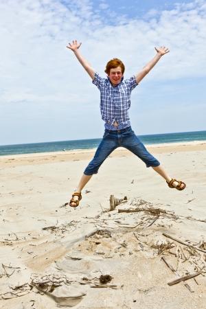 boy enjoys  the beautiful beach and jumps photo