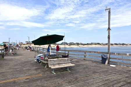 nags: NAGS HEAD, USA - JUL 18.: people enjoy fishing at the famous pier on July 18,2010 in Nags Head, USA. The first oceanfront cottage was built here around 1855 by Dr. W.G. Pool and the lenght of the pier is 750 ft.