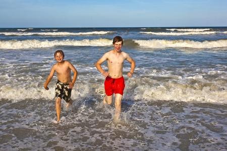 boys having fun in the beautiful clear sea photo