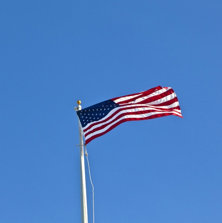 American flag waving against a brilliant blue sky photo