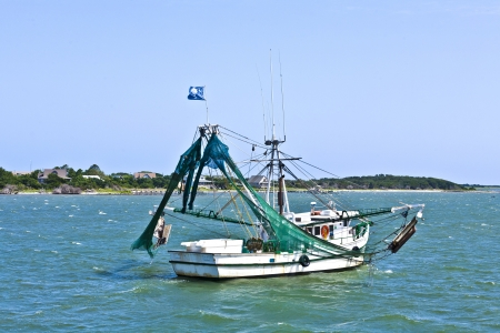 small fishing boat heading out to the ocean photo