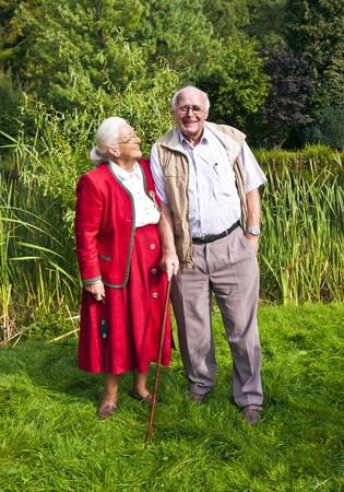 elderly couple sitting hand in hand in their garden photo