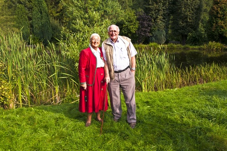 elderly couple standing happy in their garden photo