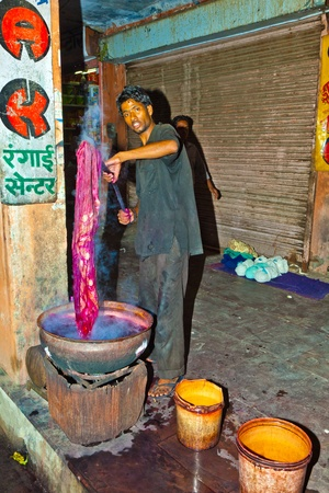 JAIPUR, INDIA - NOVEMBER 11: unidentified dyer works at outdoor factory on November 11,2011 in Jaipur, India. He dyes clothes with colors.