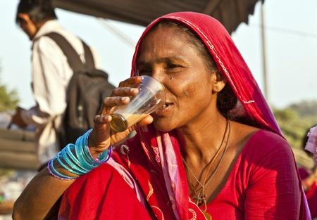 DELHI - NOVEMBER 8: woman drinking tea at the Meena Bazaar Market on November 8, 2011 in Delhi, India. Shah Jahan founded the bazaar in the 17th century inspired by the Isfahan Bazaar.