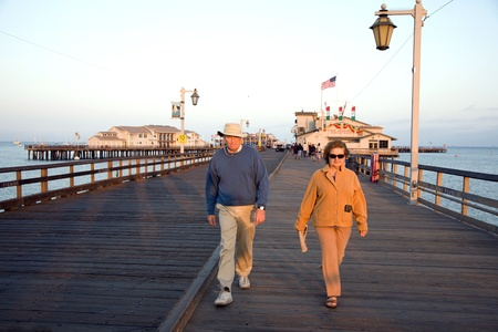 SANTA BARBARA, USA - JULY 28: people visiting scenic pier in SAnta barbara in sunset  on JULY 28, 2008 in Santa Barbara, USA. First built in 1872, the wharf ranked as the longest deep-water pier.