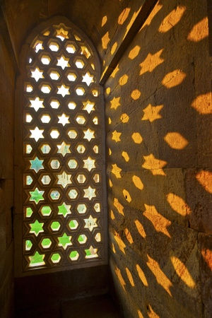 the architecture is ancient: Qutb Minar, Delhi, carvings in the sandstone of a window gives a pattern of sky with stars Stock Photo
