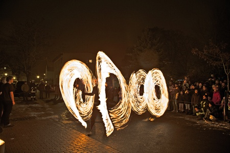 SCHWALBACH, GERMANY - DECEMBER 5: young people perform a fire spectacle at night for the audience of the Christmas Market  on December 05, 2010 in Schwalbach, Germany.