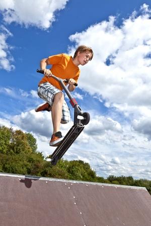 vespa: muchacho que salta sobre una rampa con su moto Foto de archivo