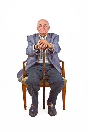 oude man zitten in de stoel met zijn wandelstok Stockfoto
