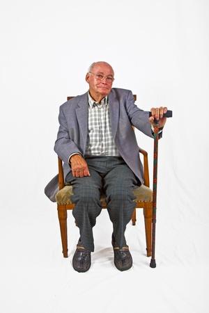 Alte Mann sitzt im Sessel mit seinem Gehstock Standard-Bild - 11758737