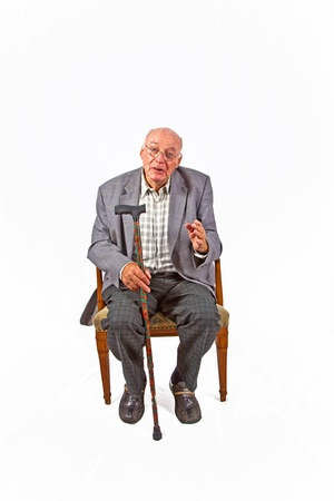 old man sitting in the armchair with his walking stick photo