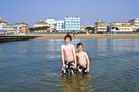 brothers in the sea at the beach of Jesolo, Venice, Italy in refreshing water photo