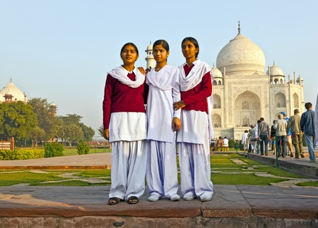 AGRA, INDIA - NOV 16:  local tourists pose for a photo at the Taj Mahal on November 16, 2011 in Agra, India. 2,5 Mio. local tourists visit the UNESCO World heritage site yearly. It is open from 6am to 7pm daily.