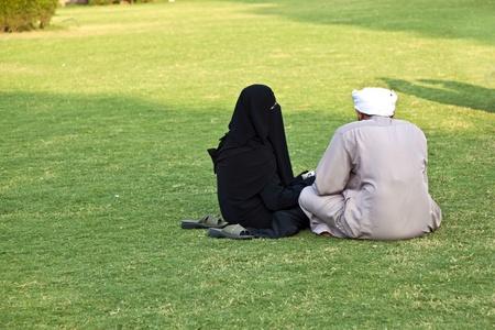 burka: donna in burka islamico seduta sul green con il marito