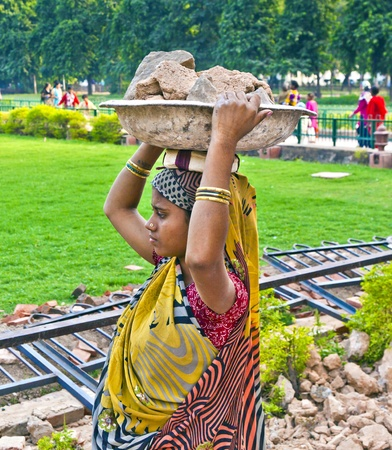 DELHI, INDIA - NOVEMBER 9: female worker carries rock waste on her hat on November 9, 2011 in Delhi, India. 2,057  Mio women work in the construction business (2004) and the figures are increasing.