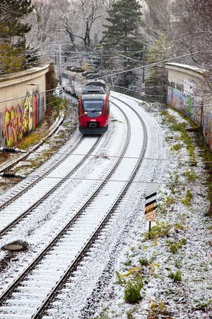 exists: VIENNA, AUSTRIA - NOV 26: OEBB train to vienna Huettendorf passes by on snow covered rails on November 26,2010 in Vienna, Austria. OEBB exists since 1947 and coveres a net of ca 5700 km in Austria.