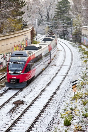 exists: VIENNA, AUSTRIA - NOV 26: OEBB streetcar in vienna passes by on snow covered rails on November 26,2010 in Vienna, Austria. OEBB exists since 1947 and coveres a net of ca 5700 km in Austria. Editorial