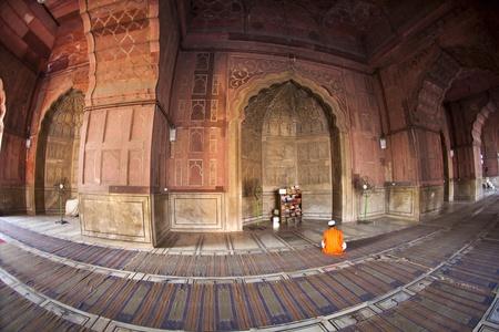 coran: man praying in the mosque Jama Masjid in Delhi