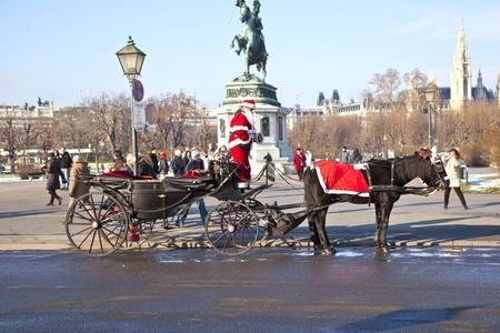 characterize: VIENA, Austria - 26 de noviembre: El controlador de la fiaker est� vestido como Santa Claus en noviembre 26,2010 en Viena, Austria. Desde el siglo 17, los carruajes tirados por caballos caracterizan Viena paisaje urbano.
