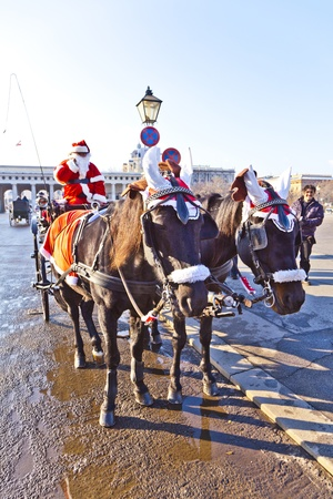 characterize: VIENNA, AUSTRIA - NOV 26: driver of the fiaker is dressed as Santa Claus on November 26,2010 in Vienna, Austria. Since the 17th century, the horse-drawn carriages characterize Viennas cityscape.