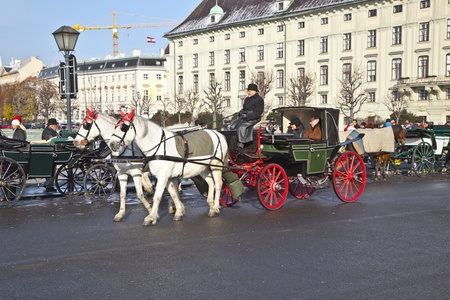 VIENNA, AUSTRIA - NOV 26: driver of the fiaker wait for tourists on November 26,2010 in Vienna, Austria. Since the 17th century, the horse-drawn carriages characterize Viennas cityscape. Stock Photo - 12059843