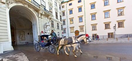 characterize: VIENA, AUSTRIA - 26 de noviembre: fiaker tirado por caballos en el Hofburg de noviembre 26,2010 en Viena, Austria. Desde el siglo 17, los carruajes tirados por caballos caracterizar Viena paisaje urbano.