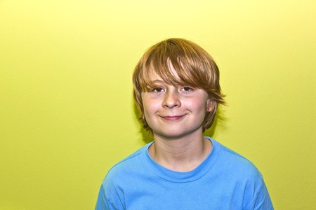 happy smiling young boy with yellow wall Stock Photo - 13506280