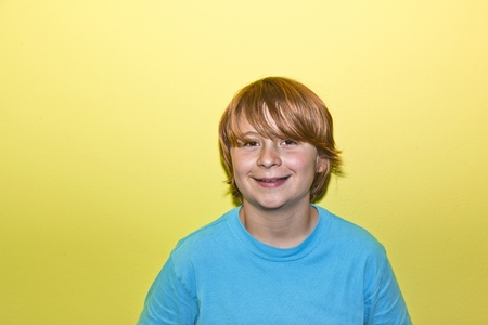 happy smiling young boy with yellow wall Stock Photo - 12609235