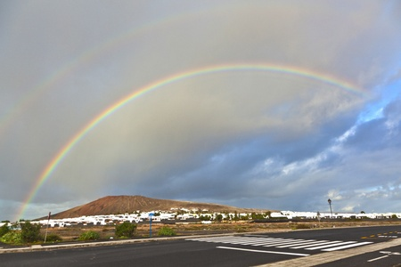 beautiful rainbow over the mountain with dark clouds photo