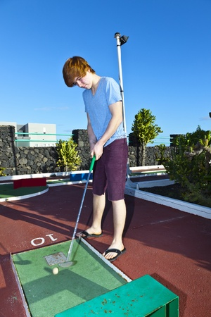 boy playing mini golf in the course photo