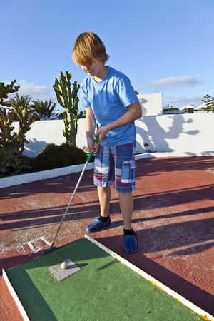 boy playing mini golf in the course Stock Photo - 12247417