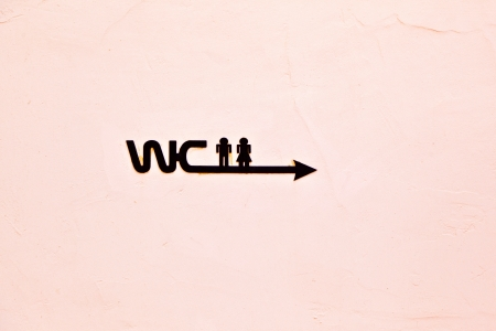 washroom: sign WC with icon of Man and woman on the concrete wall