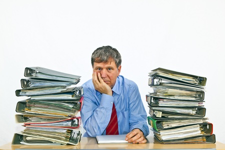 burn out: man studies folder with files at his desk in the office