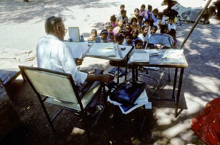 campagna: INDIA, AGRA - AUGUST 01: insegnante insegna ai bambini in aula all'aperto agosto 01,1994 in Agra, India. India si espande l'alfabetizzazione a circa due terzi della popolazione