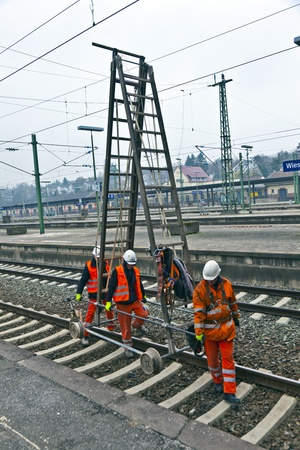 catenation: WIESBADEN, GERMANY. worker repair the catenary on February 2,2011 in Wiesbaden, Germany. Collegues save the rails to have a warn system on place.