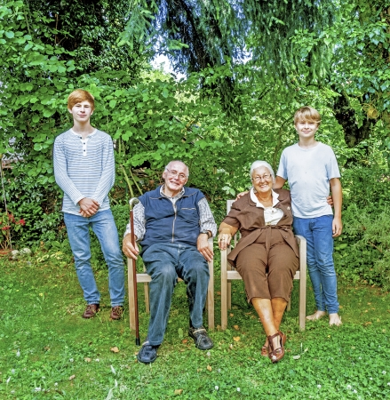 extended family group posing in the garden with grandparents photo