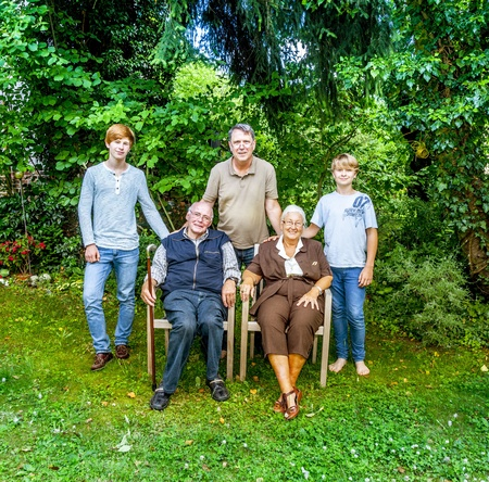 extended family group posing in the garden with grandparents