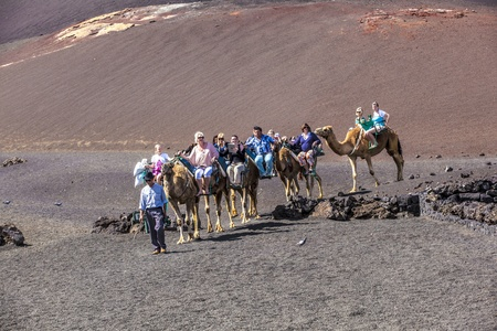 TIMANFAYA NATIONAL PARK, LANZAROTE, SPAIN - APRIL 5: Tourists ride on camels being guided by local people through the famous Timanfaya National Park in April 05,2012. Stock Photo - 13162155