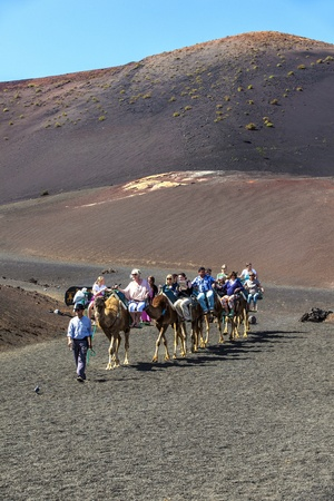 TIMANFAYA NATIONAL PARK, LANZAROTE, SPAIN - APRIL 5: Tourists ride on camels being guided by local people through the famous Timanfaya National Park in April 05,2012. Stock Photo - 13162153