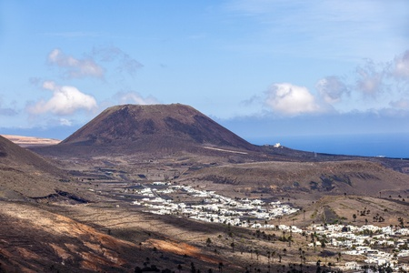 Small town of Haria in Lanzarote with palms in volcanic area photo