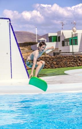 boy has fun jumping in the pool photo